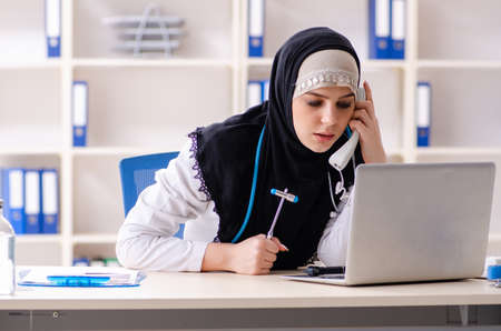 Young doctor in hijab working in the clinic Imagens