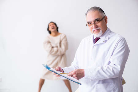 Aged male doctor psychiatrist examining young patient Stock Photo
