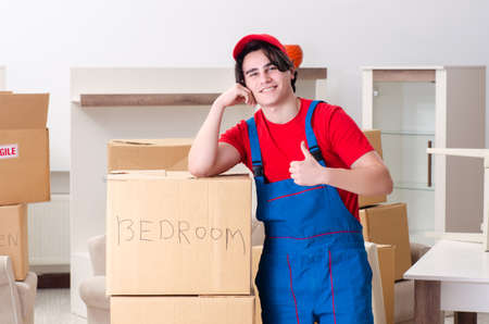 Young male contractor with boxes working indoors