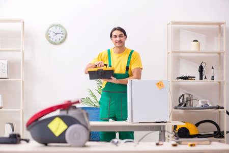 Man repairman repairing vacuum cleaner and fridge Stock Photo