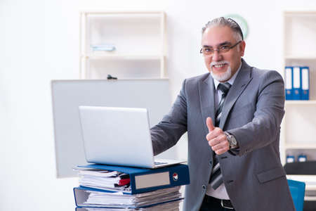 Aged male employee unhappy with excessive work Reklamní fotografie