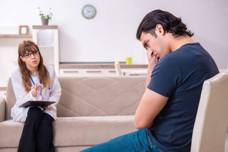 Young male patient discussing with female psychologist personal Фото со стока