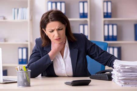 Arbeitnehmerin mittleren Alters leidet im Büro Standard-Bild