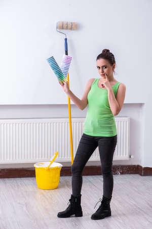 Young beautiful woman doing renovation at home Stockfoto