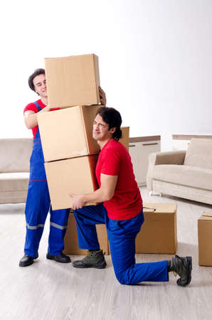 Two young contractor employees moving personal belongings