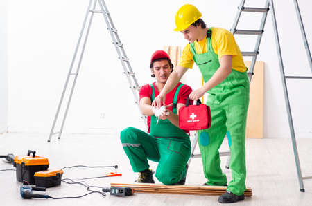 Injured worker and his workmate Foto de archivo - 124852184