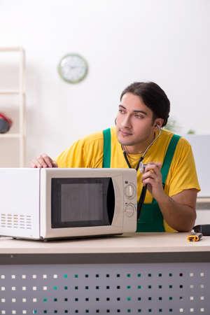 Young repairman repairing microwave in service centre Foto de archivo - 124852233