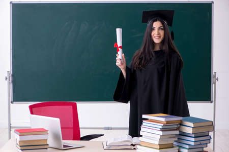 Female graduate student in front of green board Stockfoto