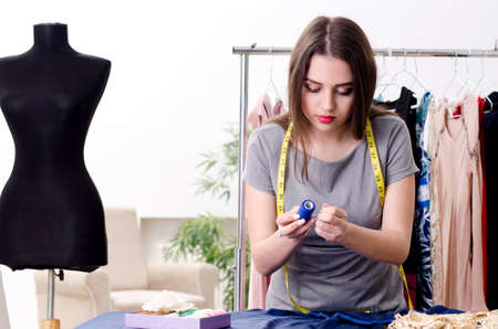 Young beautiful female tailor taking measurements Stock Photo