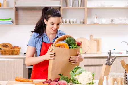 Young woman with vegetables in the kitchen Stockfoto