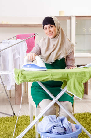 Woman in hijab doing clothing ironing at home