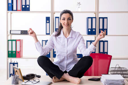 Young female employee doing exercises in the office Stock Photo