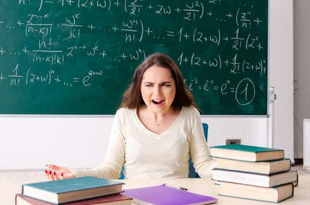 Jeune femme professeur de mathématiques devant le tableau