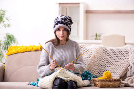 Young beautiful woman knitting at home