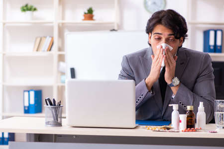 Man with flu working in the office Imagens