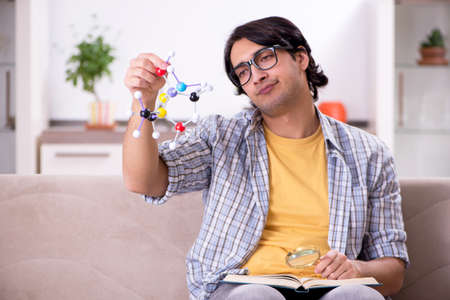 Young student physicist preparing for exam at home