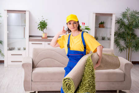Old female contractor doing housework Stock Photo