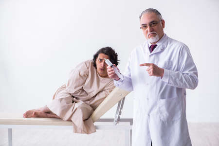 Aged male doctor psychiatrist examining young patient Standard-Bild