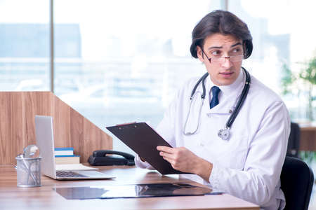 Young handsome doctor working in the clinic