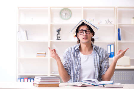 Young male student preparing for exams at home Imagens