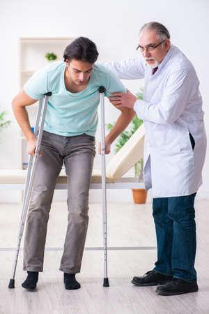 Jeune patient de sexe masculin blessé à la jambe rendant visite à un vieux médecin Banque d'images