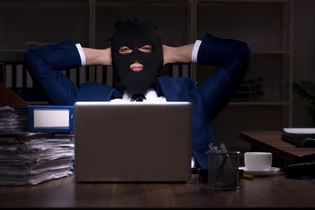 Male employee stealing information in the office night time
