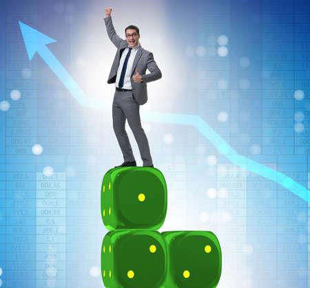 Businessman balancing on top of dice stack in uncertainty concep Banco de Imagens