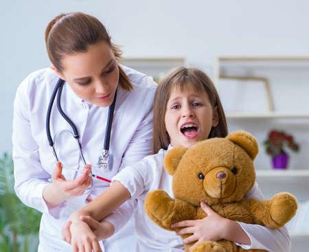 Medico femminile della donna che esamina piccola ragazza sveglia con l'orso del giocattolo Archivio Fotografico