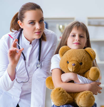 Doctora examinando a una niña linda con un oso de juguete Foto de archivo