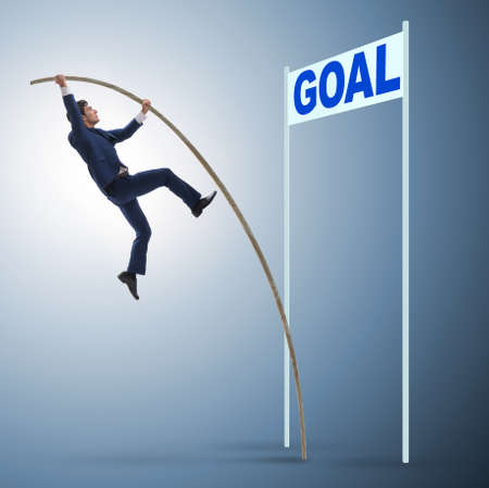 Businessman pole vaulting towards his goal in business concept Imagens