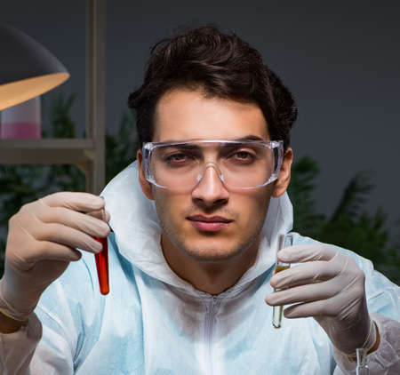 Young male doctor doing blood test late at night in overtime.