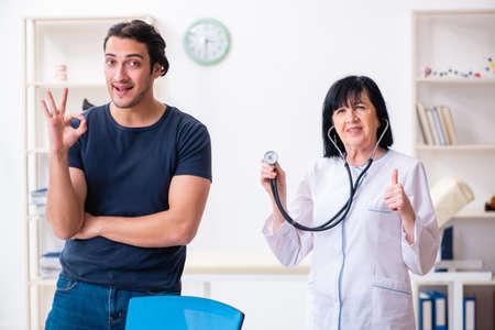 Giovane paziente maschio che visita una dottoressa anziana