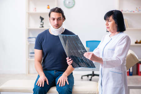 Young male patient visiting aged female doctor Stock Photo