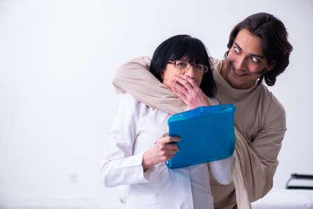 Oude vrouwelijke psychiater op bezoek bij jonge mannelijke patiënt
