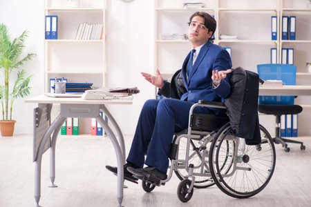 Young male employee in wheelchair working in the office