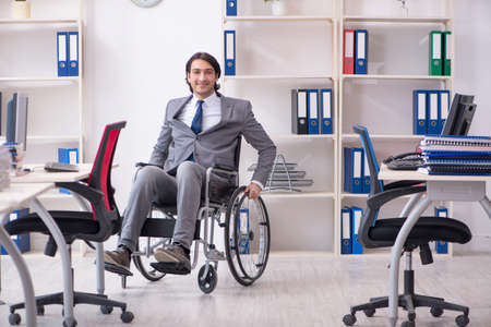 Young handsome employee in wheelchair working in the office