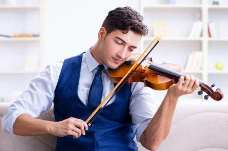 Junger Musikermann, der zu Hause Geige spielen übt