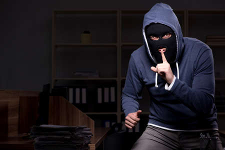 Male thief in balaclava in the office night time