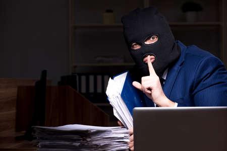Männlicher Mitarbeiter stiehlt Informationen in der Büronacht