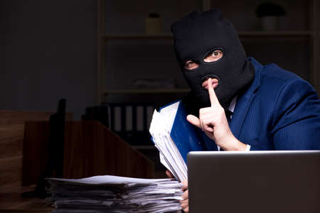 Male employee stealing information in the office night time Banque d'images