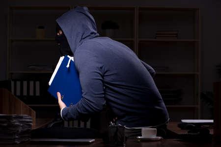 Ladrón masculino en pasamontañas en la oficina por la noche