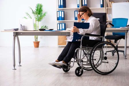 Empleada en silla de ruedas en la oficina Foto de archivo