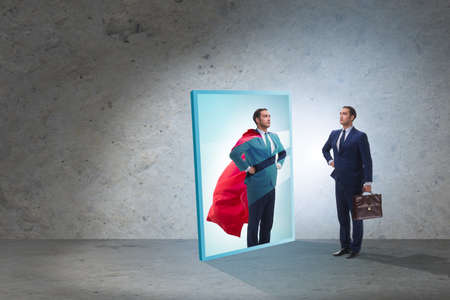 Businessman seeing himself in mirror as superhero Stock Photo