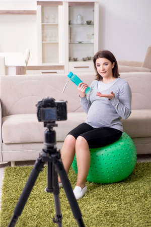 Pregnant woman blogger doing physical exercises