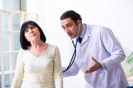 Jonge dokter die senior oude vrouw onderzoekt
