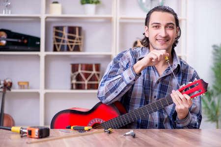 Young handsome repairman repairing guitar