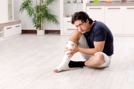Leg injured young man suffering at home Stockfoto