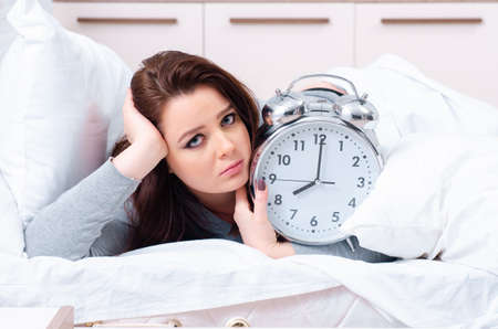 Junge Frau, die im Zeitmanagementkonzept auf dem Bett liegt