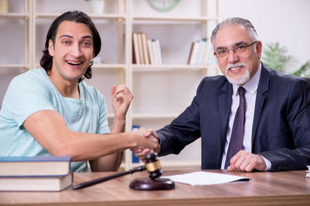 Young man visiting experienced male lawyer