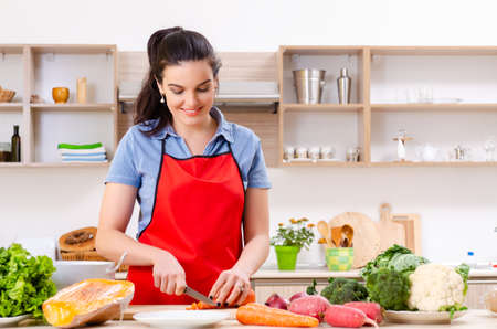 Young woman with vegetables in the kitchen 写真素材